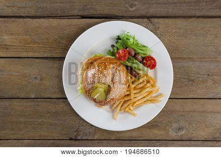 Overhead of hamburger, french fries and salad in plate on wooden table