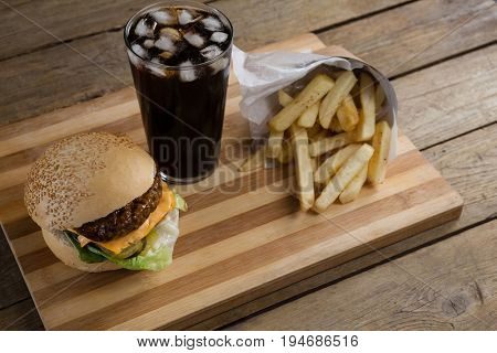 Overhead of hamburger, french fries and cold drink on table
