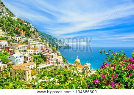 beautiful view on Positano on Amalfi coast with blurred flowers on foreground Campania Italy. focus on background