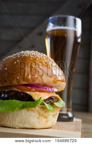 Burger with glass of beer on chopping board
