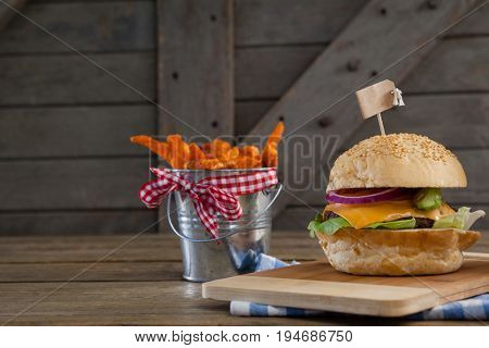 Hamburger and french fries on table against wooden background