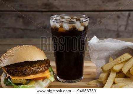 Close-up of hamburger, french fries and cold drink on table