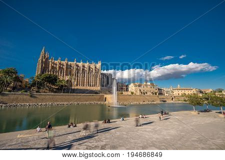 Panoramic view Palma de Mallorca Cathedral blue sky reflected in water Tourists and people walking and taking photos. Balearic islands of Spain