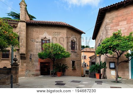Traditional medieval square with citrus trees in Spanish village (Poble Espanyol) at Barcelona town, Catalonia, Spain
