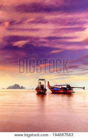Traditional long-tail boat on the beach in Thailand at sunset