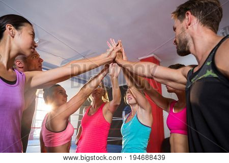 Low angle view of young athletes giving high-fives at fitness studio