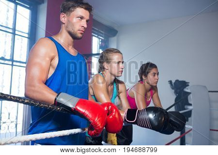 Young male boxer standing by female athletes in boxing ring