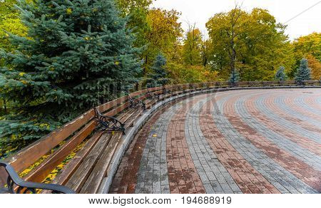 Autumn park with benches and an area