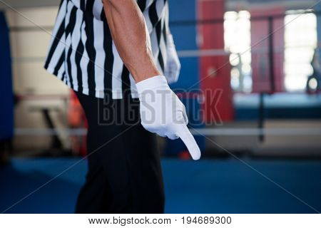 Midsection of male referee pointing down while standing in boxing ring