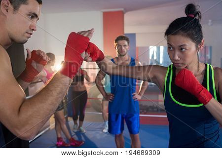 Young female boxer practicing with male in boxing ring