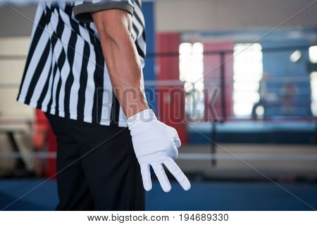 Midsection of male referee gesturing with hand while standing in boxing ring