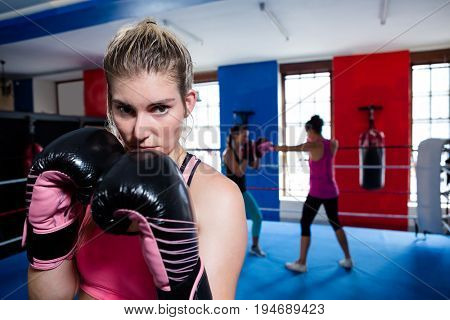 Young female boxer standing in boxing ring at fitness studio