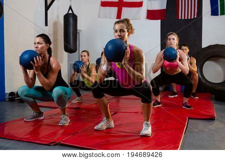 Young athletes crouching with exercise balls on mats at fitness studio