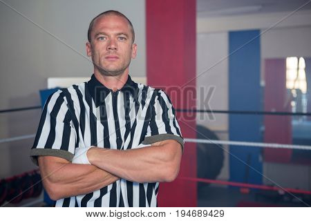 Portrait of male referee standing in with arms crossed in boxing ring