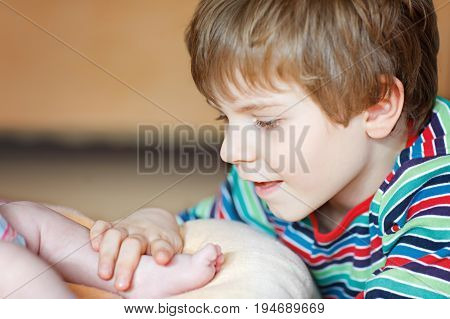 Little kid boy kissing and playing with foot of newborn baby. Brother cuddling with new born child, sister at home. Happy siblings, carefree childhood, family, love, tenderness.
