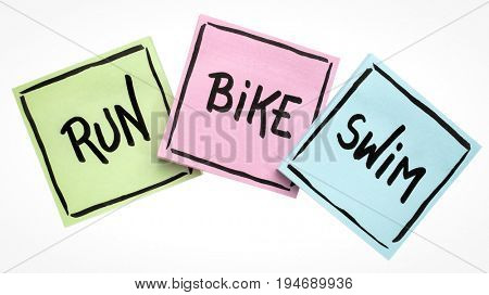 run, bike, swim - triathlon or fitness concept - handwriting in black ink on sticky notes isolated on white