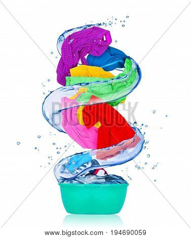 Colorful clothes rotates in a swirl and flying out from wash bowl isolated on white background