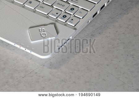 A Compact Sd Memory Card Lies On A White Netbook. The Digital Information Storage Device Is Ready Fo