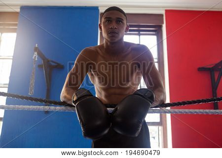 Determined man leaning on rope in fitness studio