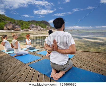 fitness, sport, yoga and healthy lifestyle concept - group of people exercising in reverse prayer pose over exotic tropical beach background