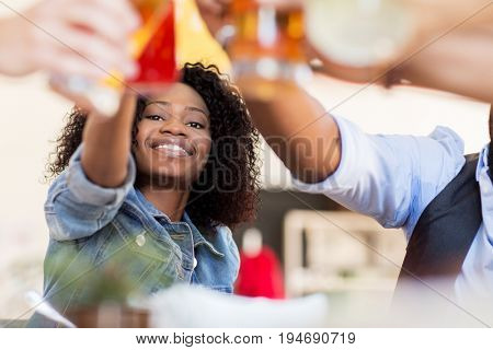party, celebration and people concept - group of happy international friends clinking drink glasses at restaurant table