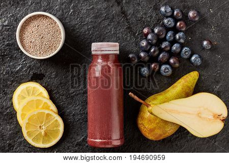 Fresh fruit smoothie with blueberries, lemon and pear with chia seeds blended and served in a bottle surrounded by the ingredients on a textured black background viewed from above