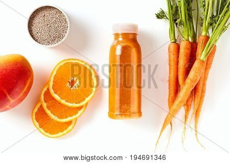 Healthy carrot, mango and orange smoothie with chia seeds for an energising breakfast in an overhead view of the blended beverage in a bottle with ingredients