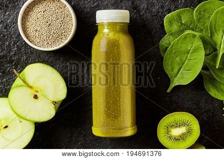 Fresh spinach, kiwifruit and apple smoothie with chia seeds for an energising breakfast with the ingredients surrounding a bottle of blended beverage on a textured black background
