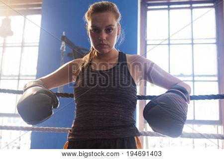 Portrait of confident woman standing in boxing ring