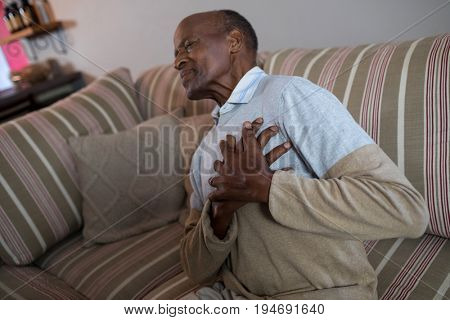 Senior man with hands on chest while suffering from chest pain