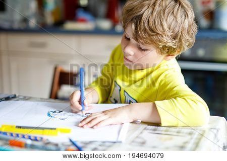 Adorable preschool kid boy painting with colorful pencils. Little child drawing a police car. Kid having fun at home or school.