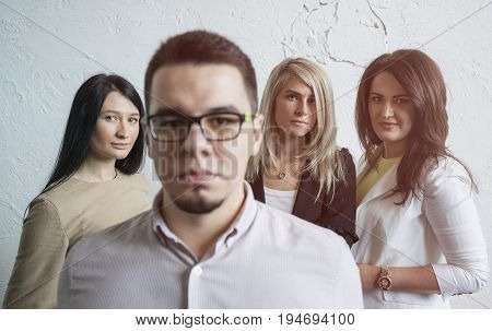Serious young man stands in the foreground against the background of three beautiful girls. Working in a team, serious attitude to work. Portrait