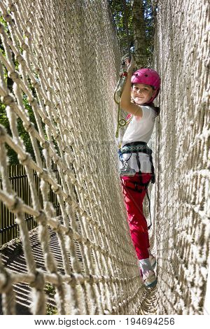 Young girl in harness climbing and trying facilities in an adventure rope park.