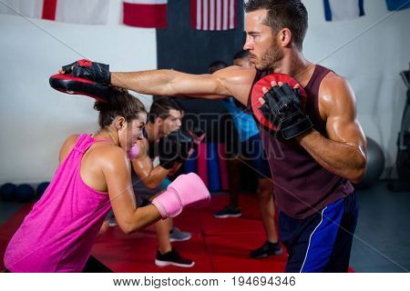 Female boxer defending with instructor at fitness studio