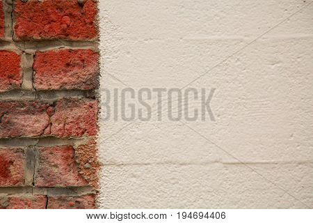 Weathered old bricks opposed new white wall