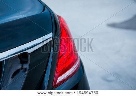 Auto. Red Taillight Of A Black Luxury Car.