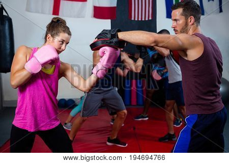 Female boxer and instructor practicing with boxing in fitness studio