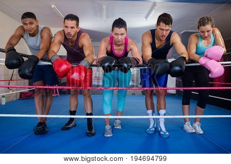 Exhausted young boxers leaning on rope in boxing ring