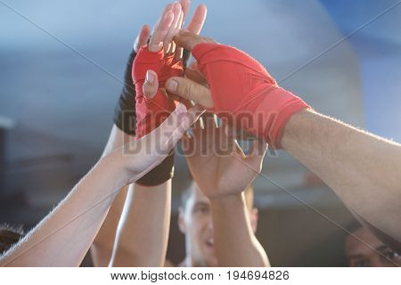 Young boxers giving high-fives at fitness studio