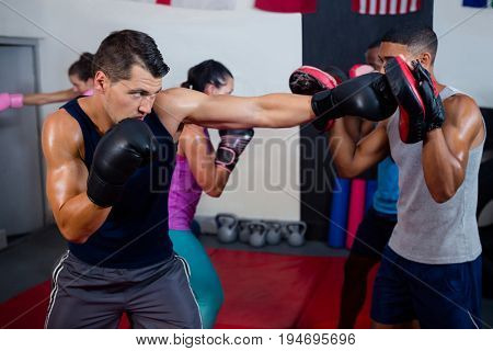 Male boxer and instructor practicing with boxing in fitness studio