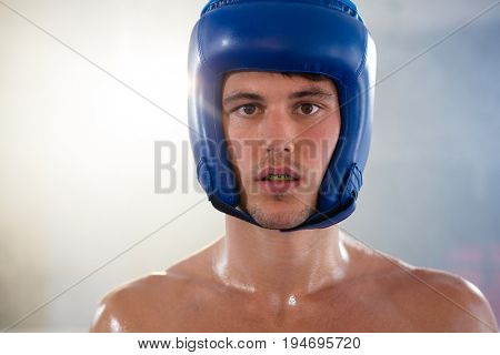 Close-up portrait of young male boxer wearing blue headgear at fitness studio