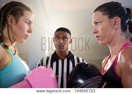 Young female boxers looking at each other against referee at fitness studio