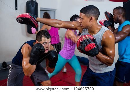 Boxer defending with male instructor at fitness studio