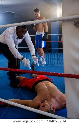 Referee counting by unconscious male boxer in boxing ring