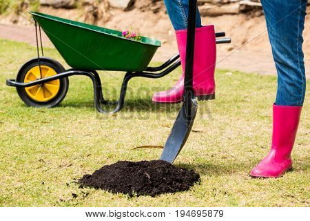 Low section of woman in pink boots with shovel standing at lawn
