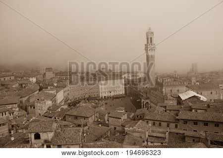 Italy Siena - December 26 2016: the view of Torre del Mangia in Piazza del Campo and red roofs of Siena in the thick fog on December 26 2016 in Siena Tuscany Italy.