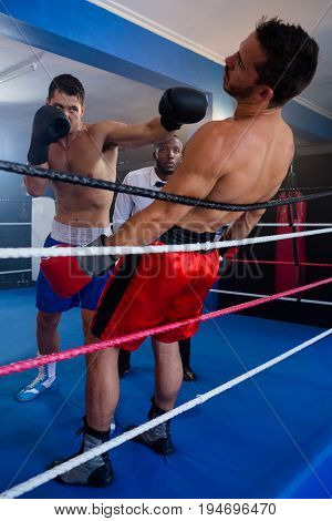 Young boxer punching male competitor in boxing ring