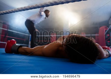 Unconscious male boxer lying by referee in boxing ring at fitness studio