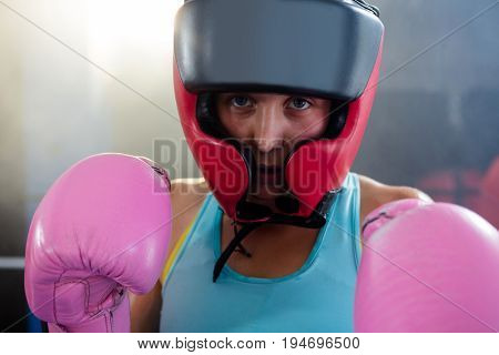 Close-up portrait of female boxer wearing protective headgear and pink gloves at fitness studio