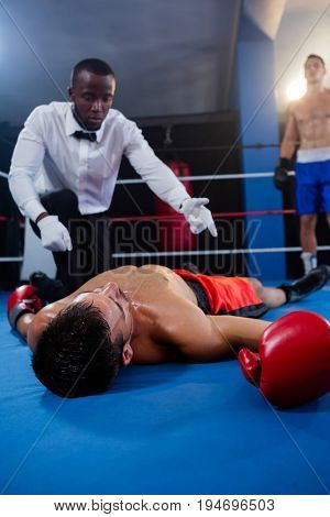 Male boxer looking while referee counting by athlete in boxing ring